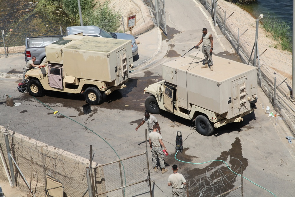 Troops clean vehicles on Victory Base Complex