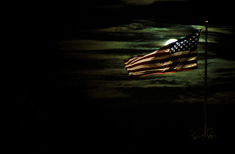 American flag lit by a full moon