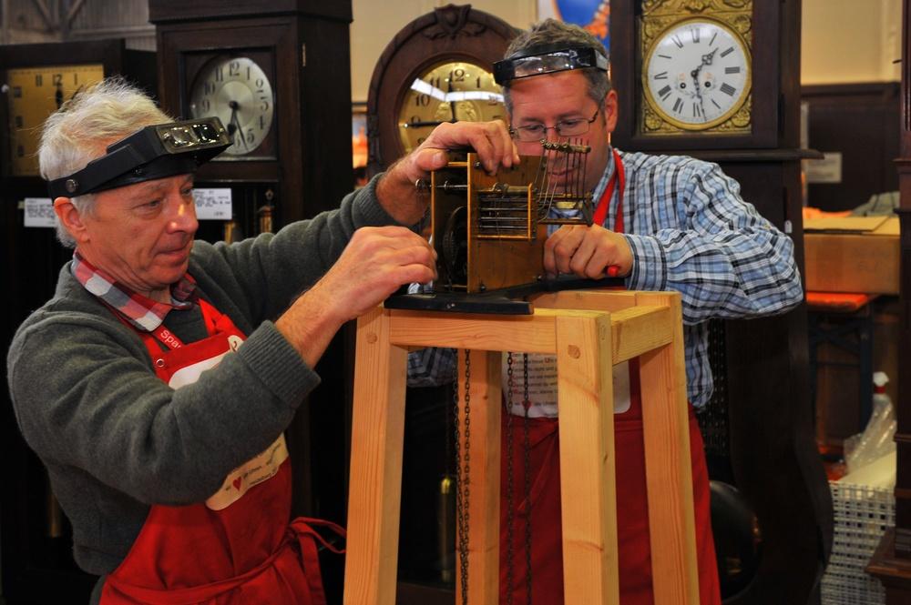 Clocksmiths repair a grandfather clock