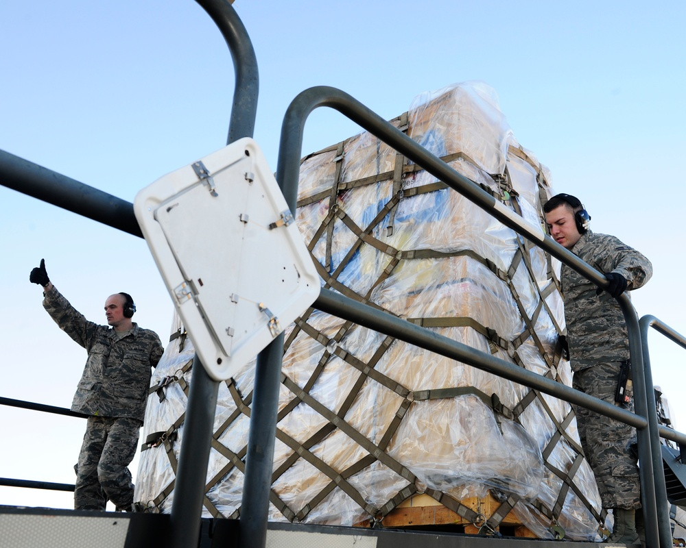 728th Air Mobility Squadron members process cargo from a C-17 Globemaster III
