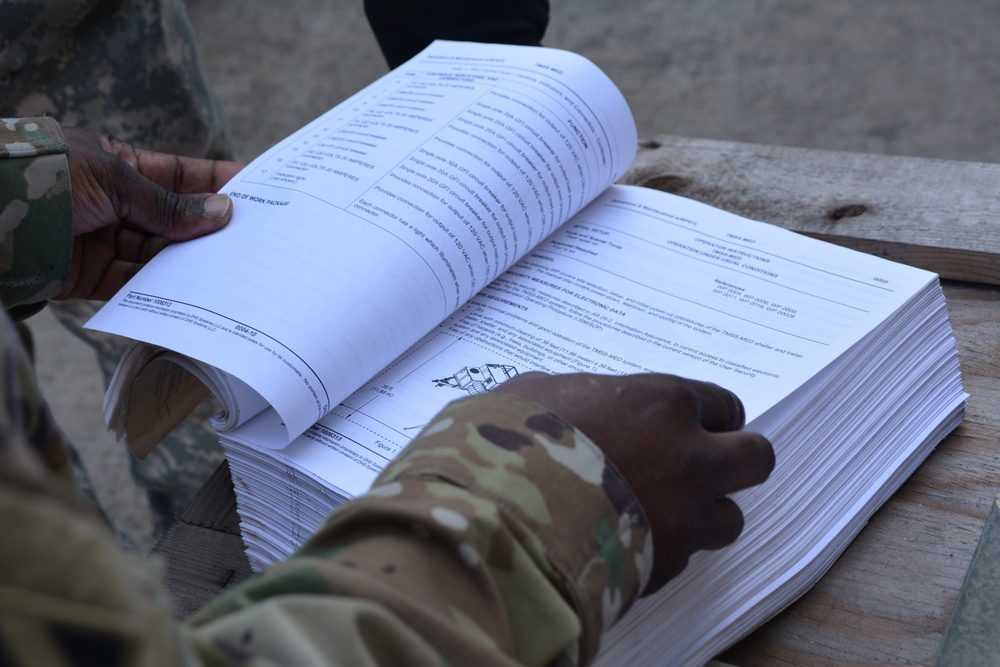 A soldier consults the technical manual to troubleshoot an 18K generator.