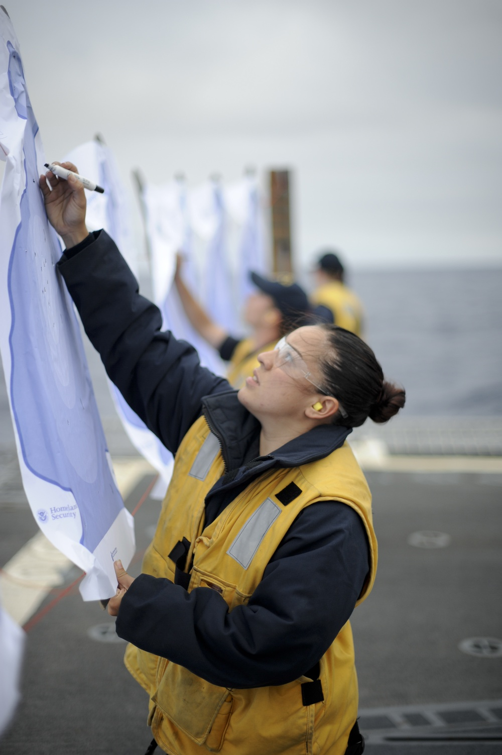 160815-N-LI612-334 PACIFIC OCEAN (August 15, 2016) Fire Controlman 2nd Class Maria Holbrook calculates points during a small arms gun shoot on the flight deck of the Arleigh Burke-class guided-missile destroyer USS Shoup (DDG 86) . Shoup is currently unde