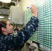 Hospital Corpsman 1st Class Ashley Gibson writes injury statuses on a white board in medical triage aboard the amphibious assault ship USS Bataan (LHD 5).