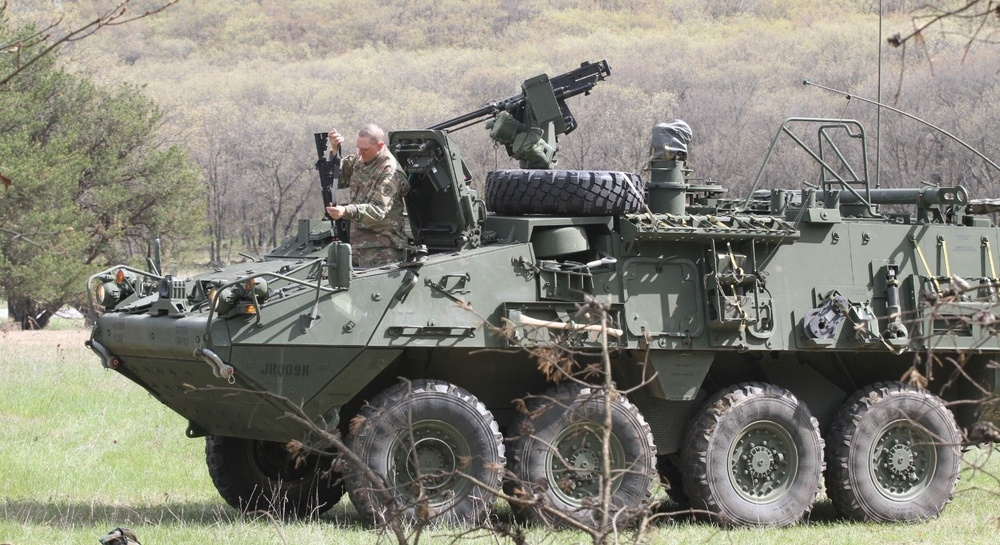 Soldier dismounts from the driver's hatch of an M1126 Stryker combat vehicle
