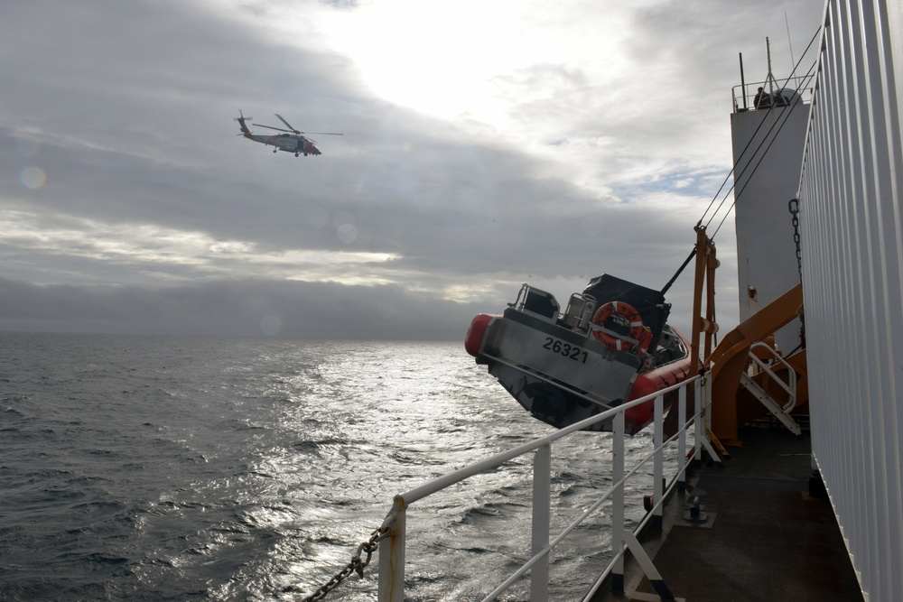 MH-60 Jayhawk helicopter transits above the Coast Guard Cutter Healy