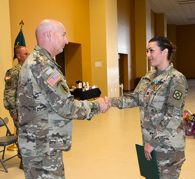 Capt. Erin Montoya, outgoing commander of the 200th Public Affairs Detachment, 93rd Troop Command, New Mexico Army National Guard, shakes hands with Col. Michael A. Treadwell, 93rd Troop Command commander.