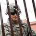 A Soldier Secures Concertina Wire to a Fence