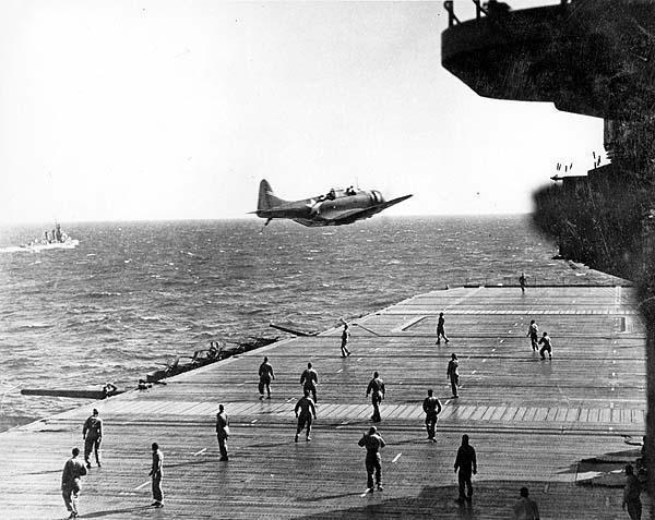 "U.S. Navy Douglas SBD Dauntless drops a message container known as a ""bean-bag"" on the flight deck of USS Enterprise (CV 9)"