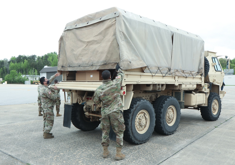 Soldiers secure a load of protective facemasks on a Light Medium Tactical Vehicle