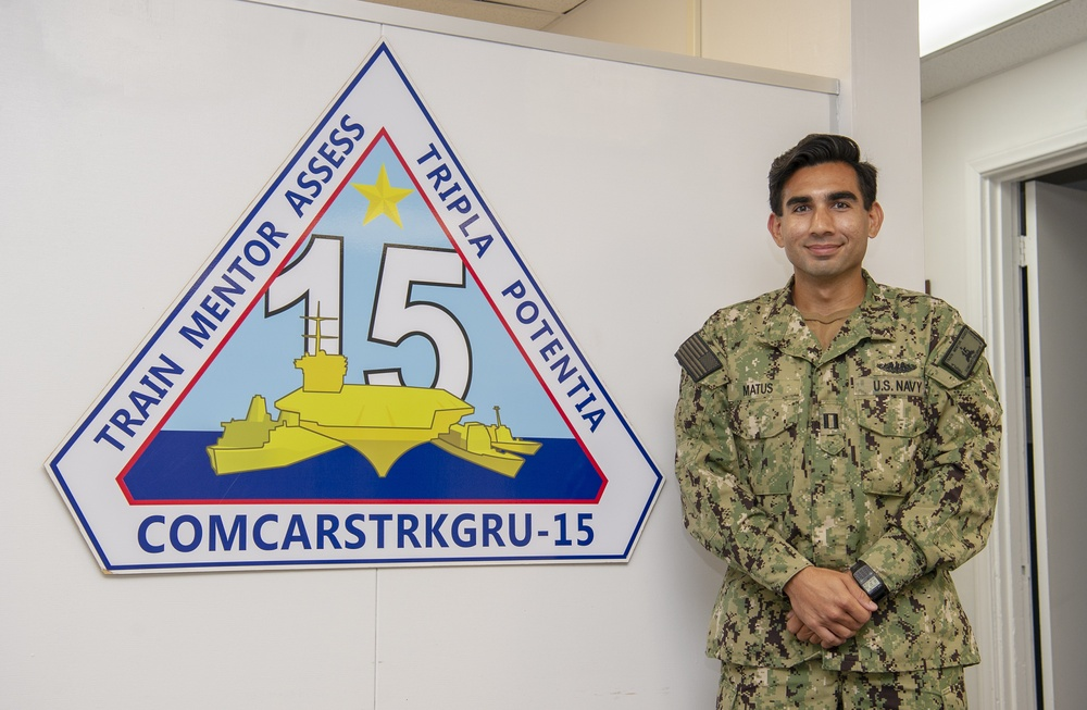 Lt. Anthony Matus stands in front of the entrance of Commander, Carrier Strike Group (CCSG) 15
