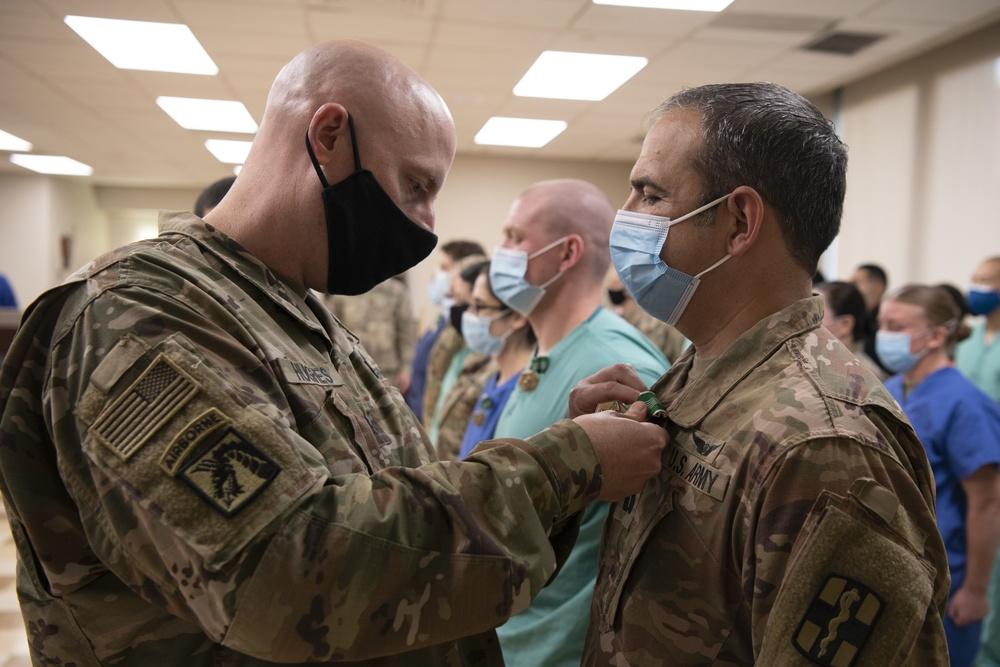 U.S. Army Lt. Col. Jason Hughes, commander, Urban Augmentation Medical Task Force - 627 presents an award at Baptist Medical Center