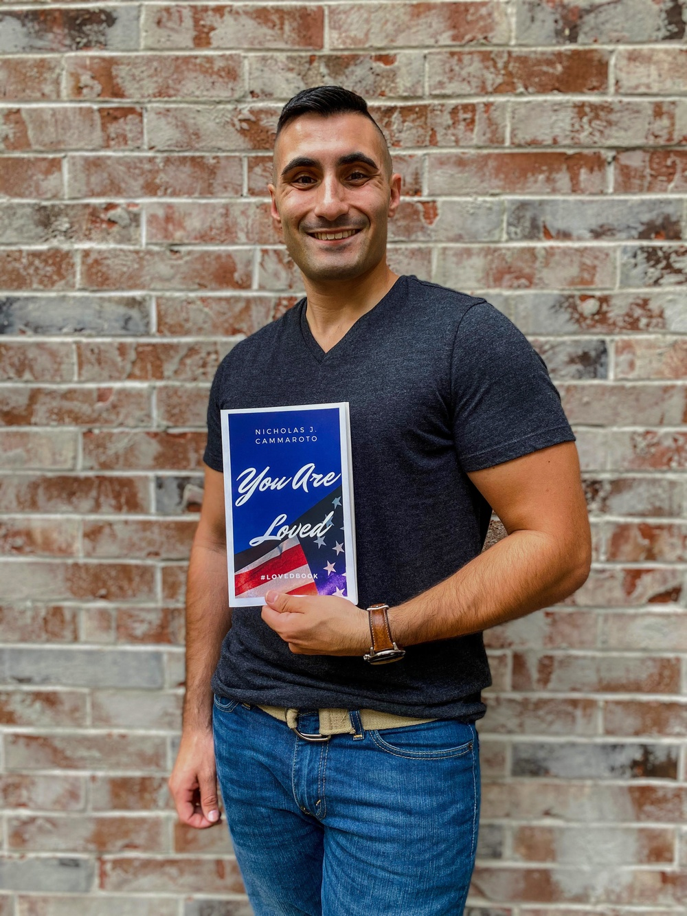 """Air National Guard Senior Airman Nicholas Cammaroto poses with a copy of his debut book, """"You Are Loved"""""""