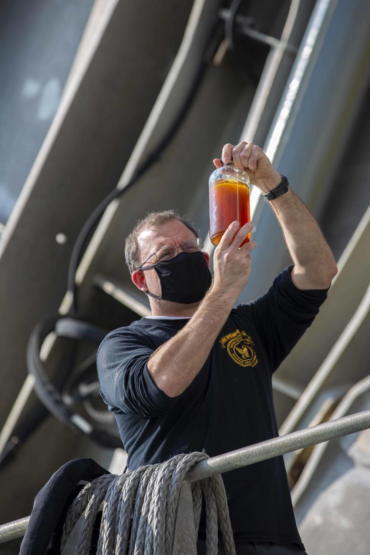 Chief Engineer onboard USNS Yuma checks fuel