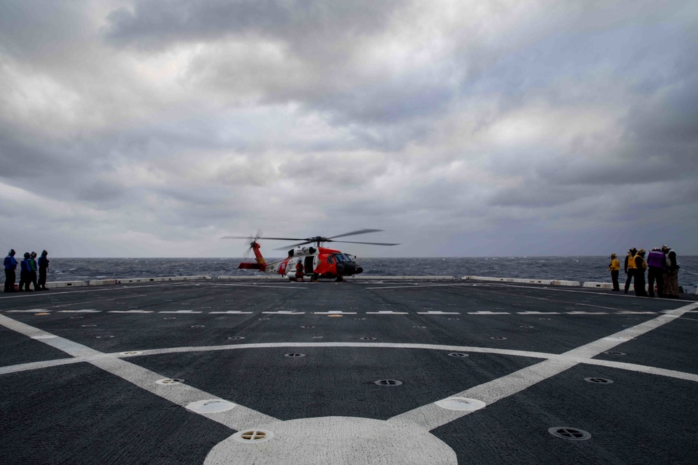 U.S. Coast Guard helicopter refuels aboard USS Arlington after a medical evacuation