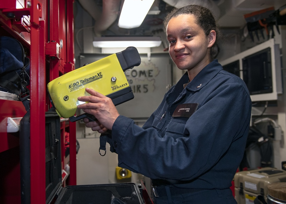 Damage Controlman 3rd Class Lareesa Garza, from Fayetteville, N.C., inspects a Naval Firefighter Thermal Imager (NFFTI) during routine maintenance