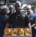 Culinary Specialist 3rd Class Marcus Davis presents fresh-baked bread with his culinary team members