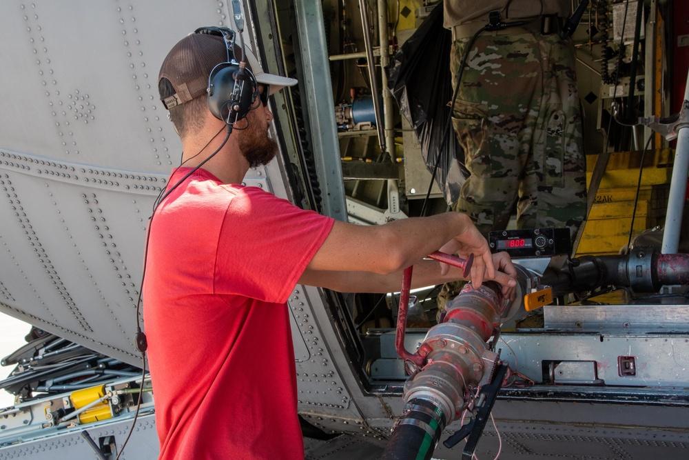 A CAL FIRE employee loads an Air National Guard C-130 with retardant at McClellan Air Tanker Base, Sacramento, Calif.
