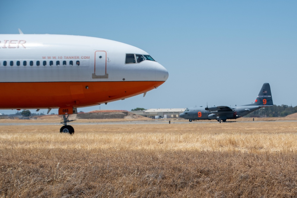 FIREFIGHT: Air National Guard C-130, MAFFS 9 out of Reno, Nev. returns to McClellan Air Tanker Base, Sacramento, Calif. as a 10 Tanker Air Carrier DC-10 launches