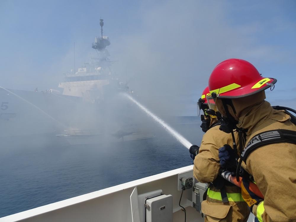 Coast Guard Cutter Benjamin crew members work to extinguish a vessel fire off the San Diego coast