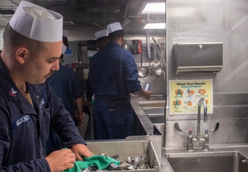Sailors work in the galley aboard USS Jackson