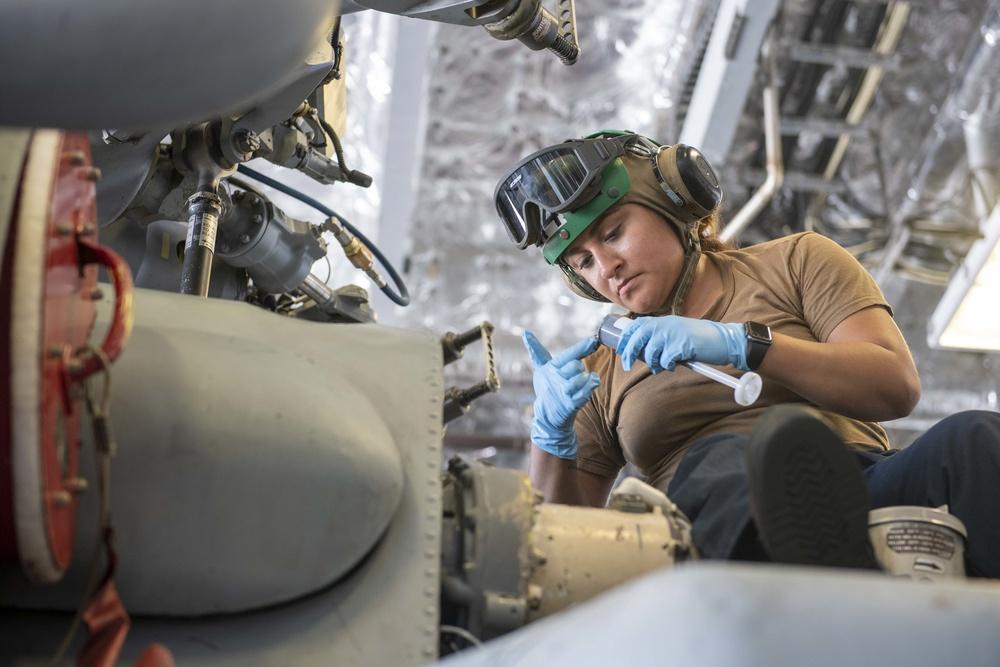 Helicopter Sea Combat Squadron (HSC) 23 Sailor applies sealant to bolt