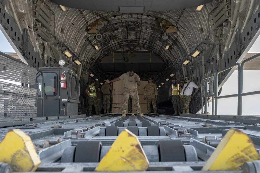 U.S. Air Force Loadmaster Guides A Container Loader
