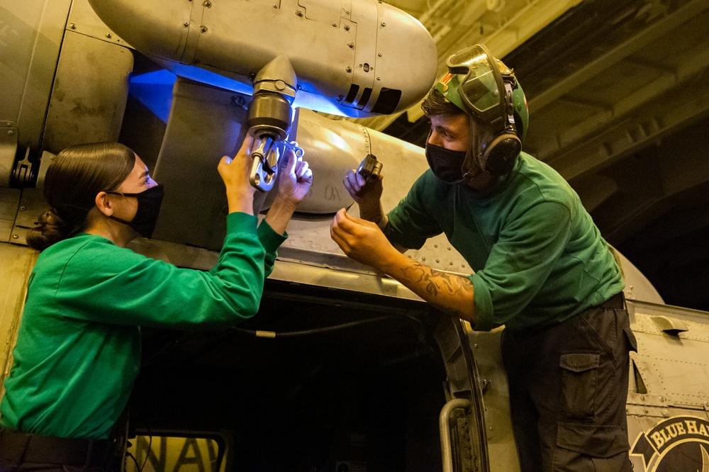 Aviation Structural Mechanic conduct maintenance on an MH-60R Sea Hawk