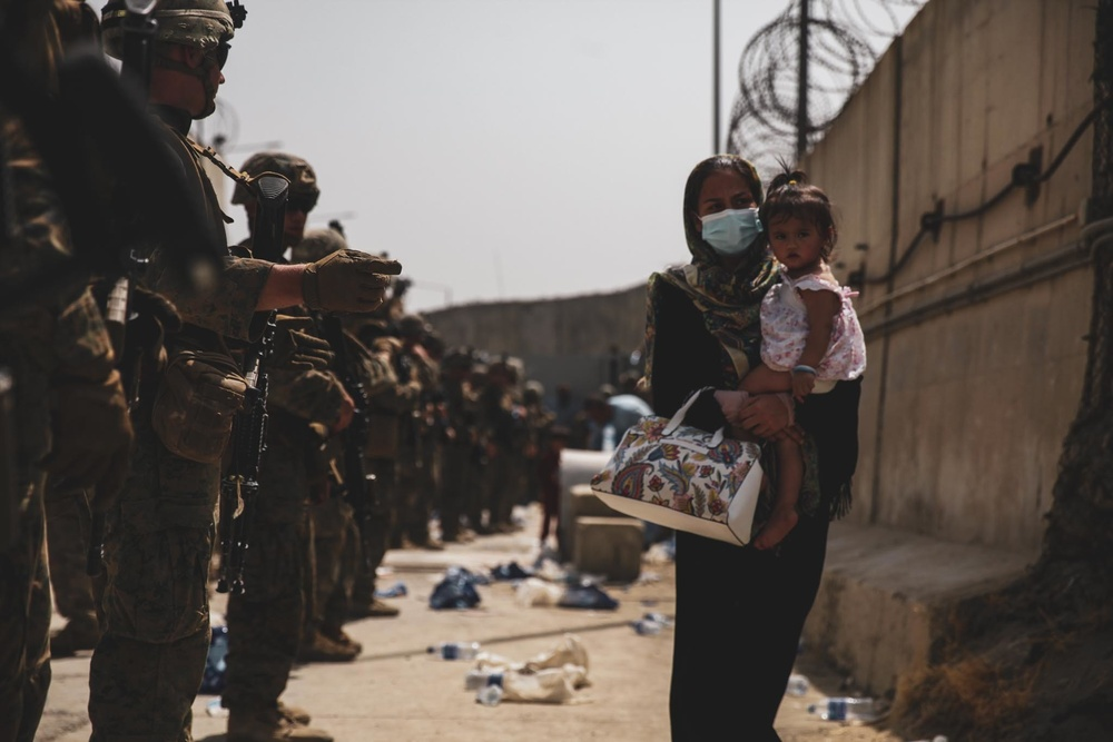 Marines with the 24th Expeditionary Unit (MEU) guide an evacuee during an evacuation at Hamid Karzai International Airport