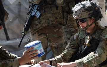 Paratrooper with the 82nd Airborne Division Places Baby Formula into one of the Care Bags [Image 5 of 5]
