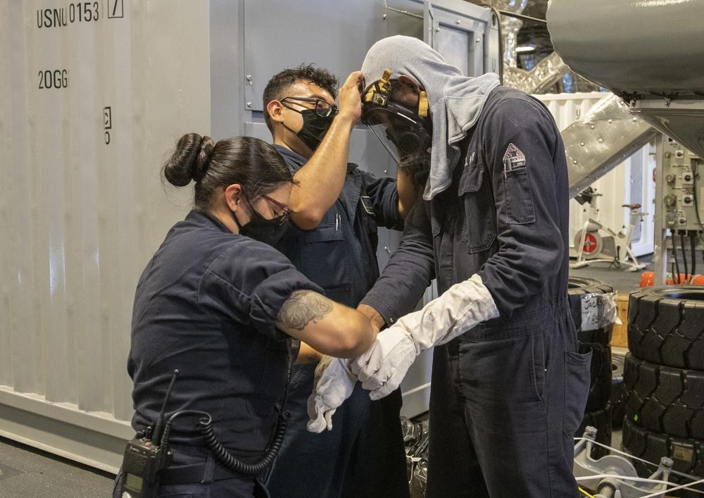 USS Jackson (LCS 6) Sailors put on fire fighting gear