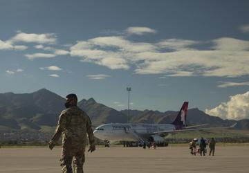 1st Armored Division soldiers help arriving Afghan evacuees