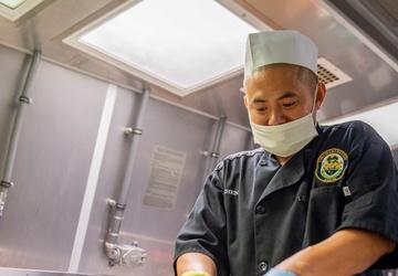 USS Charleston Sailor Prepares Meal