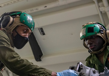 Airman Ousainou Jammeh and AD2 Sirkaylon Morgan Conduct Preventive Maintenence on an MH-60R Helicopter